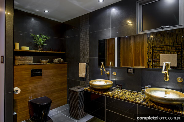 Bathroom with black toilet and gold basins